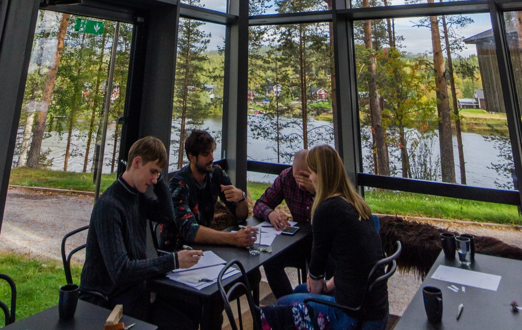 A group of researchers solve a science problem together in a glass building surrounded by trees, next to a river